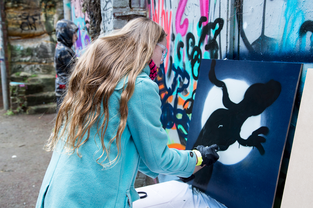 Photo of woman spray painting at the Streetsmart event