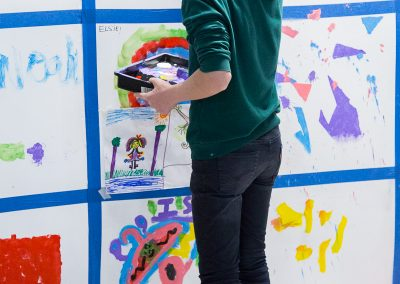 Photo of man painting onto the wall inside the Observer Building at the Streetsmart event