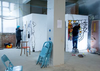 Photo of people painting onto the walls inside the Observer Building at the Streetsmart event