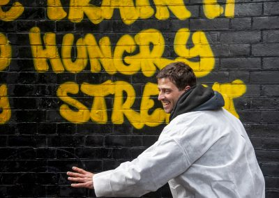 Photo of Pablo Allison spray painting onto the Alley wall has work called The Beast of the Train