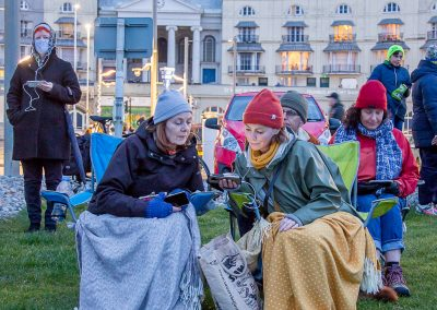 Audience watching Semaphore on mobiles on Hastings beach