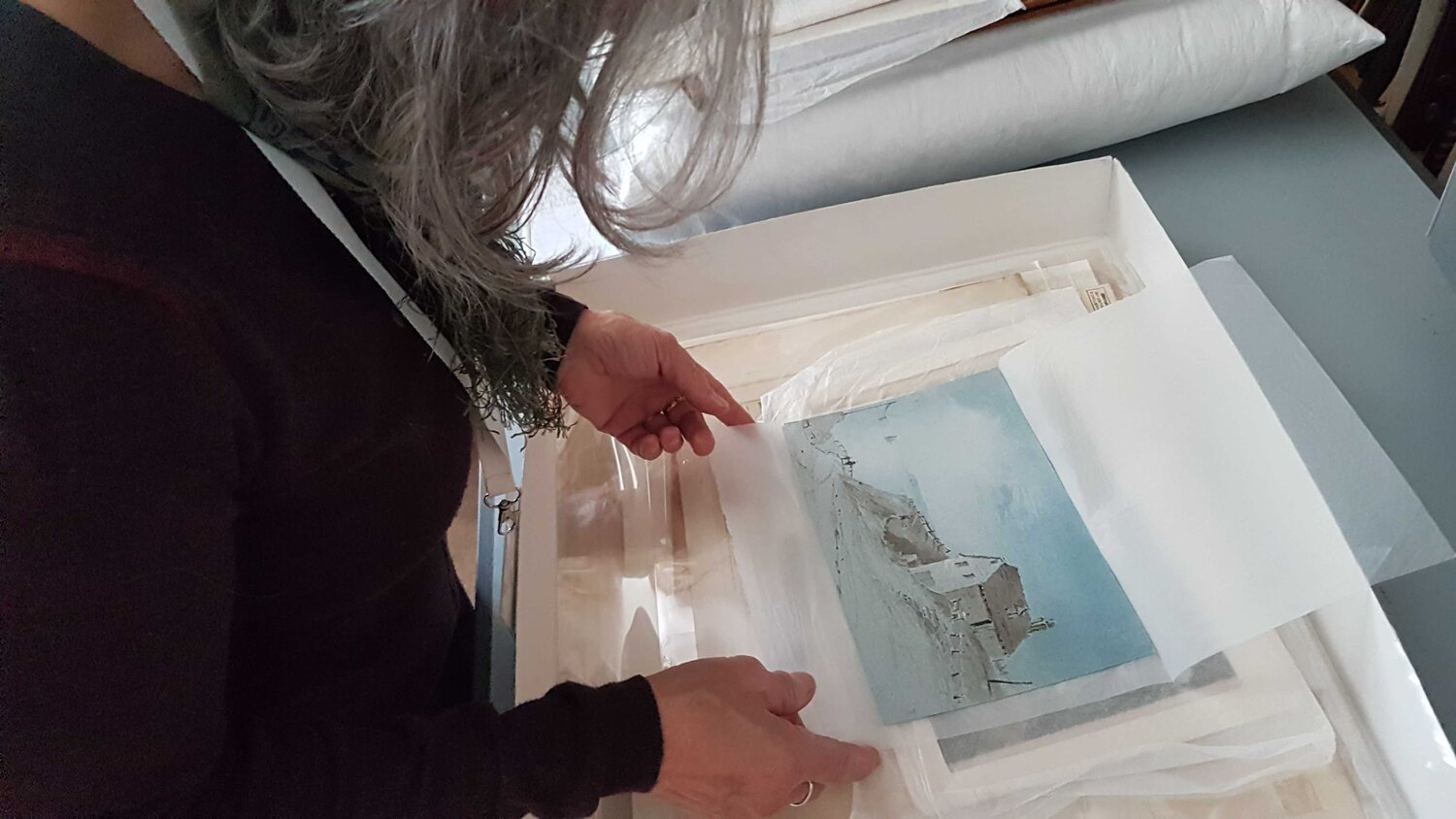 Photo of woman looking at a small landscape painting at one of the Our Present, Our Future workshops